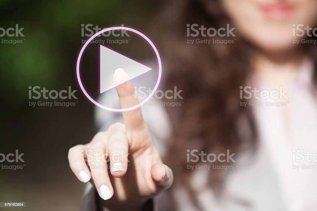 Finger pressing play button on touch screen. stock photo