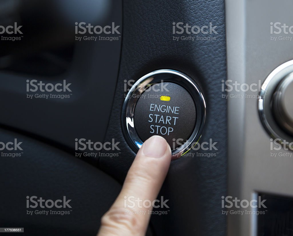 finger pressing the Engine start stop button stock photo