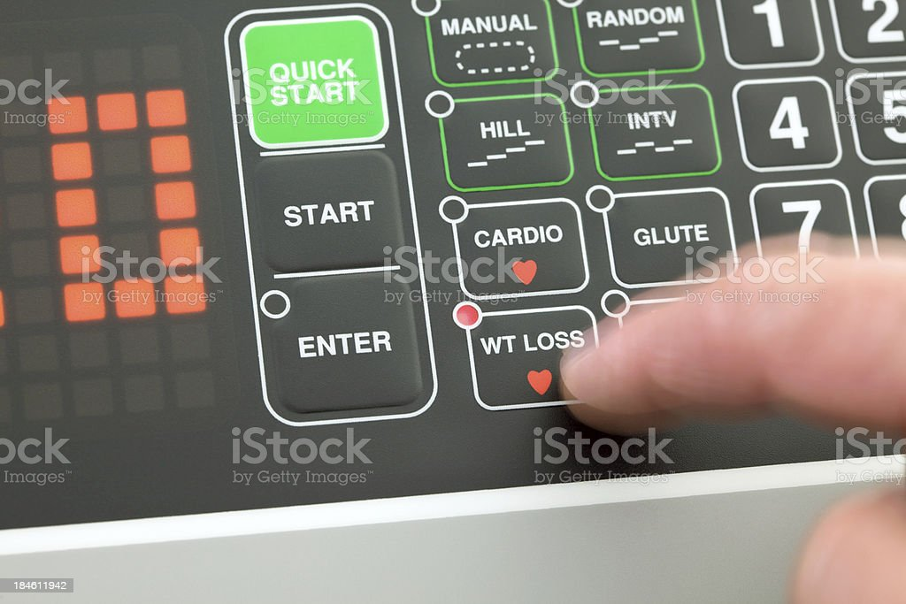 Finger Pressing Weight Loss Program Button on a Treadmill royalty-free stock photo