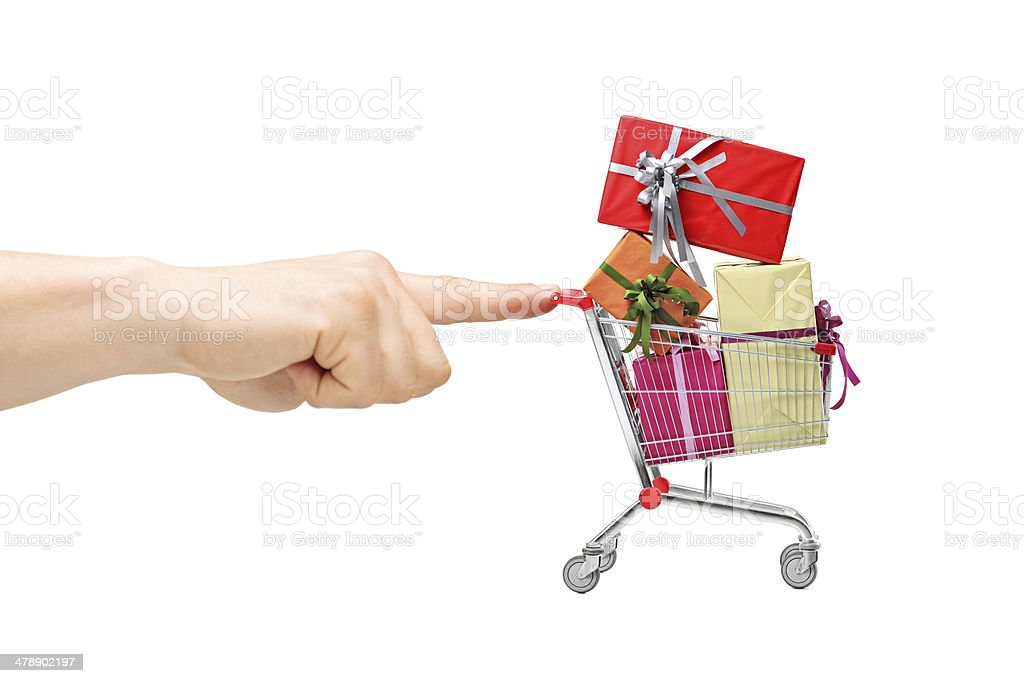 Finger pushing a shopping cart with presents stock photo