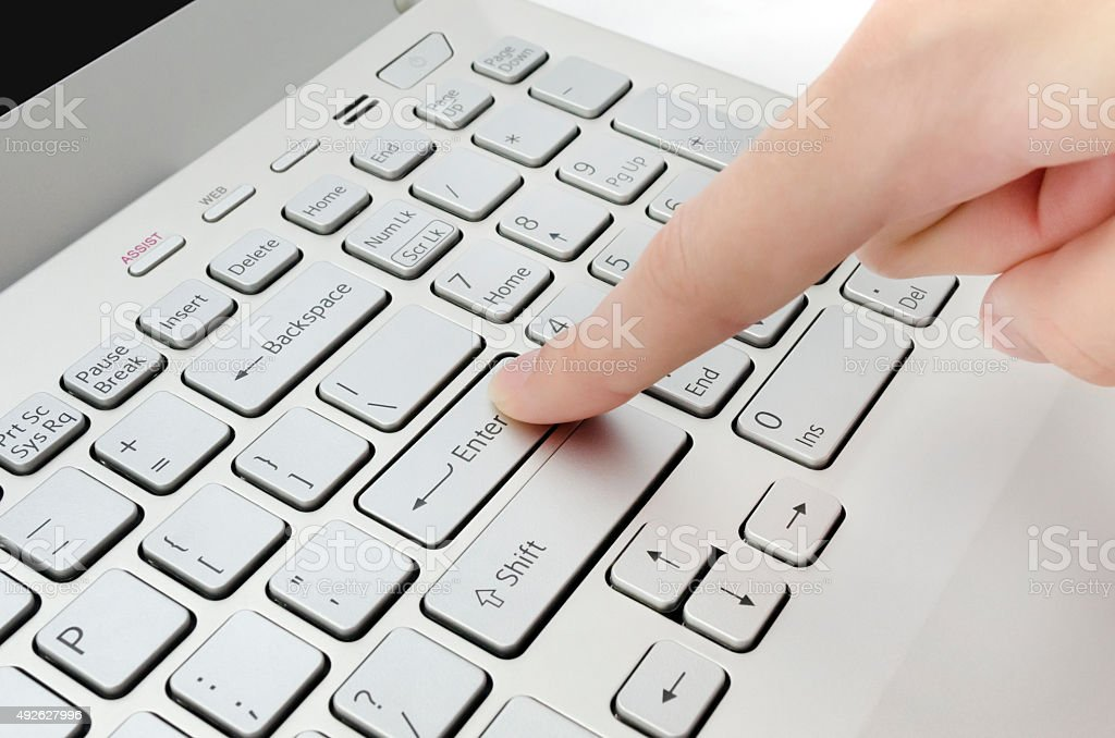Finger pushing enter button stock photo