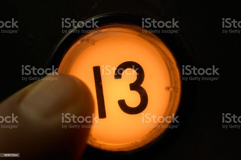 Finger pushing floor 13 elevator button stock photo