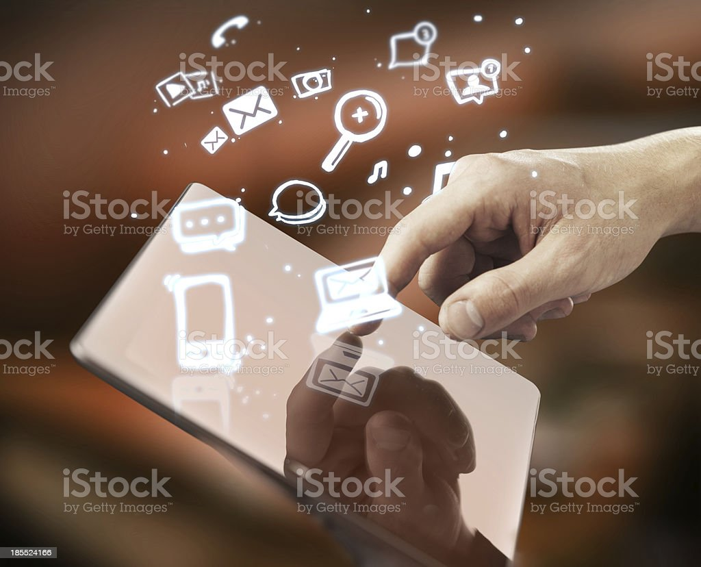 Finger pushing on a tablet with icons flying out royalty-free stock photo