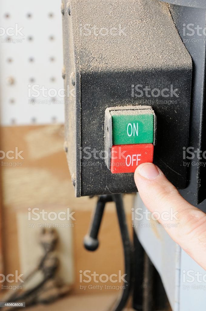 Finger pushing power tool off switch stock photo