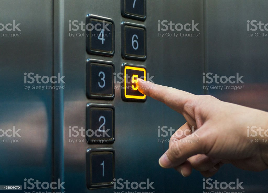 finger pushing the elevator button stock photo