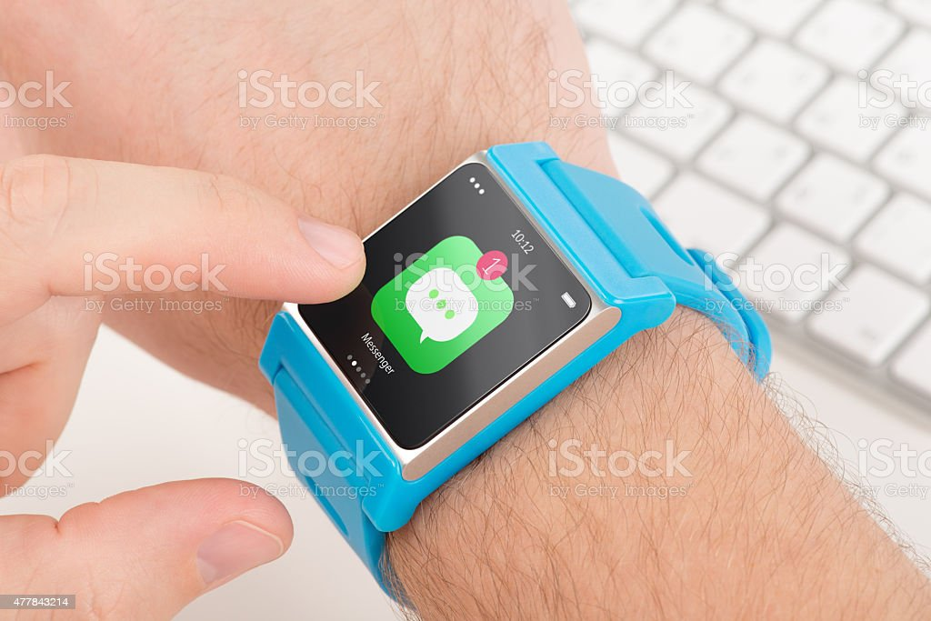 Finger taps messenger icon on blue smart watch stock photo