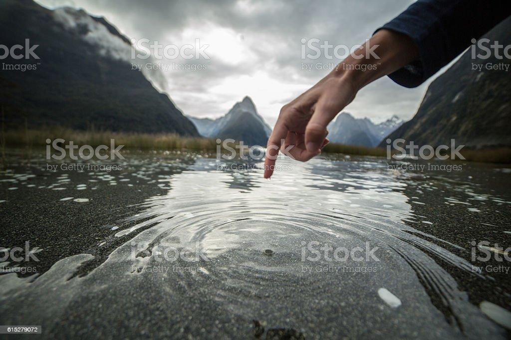 Finger touches surface of mountain lake, New Zealand stock photo