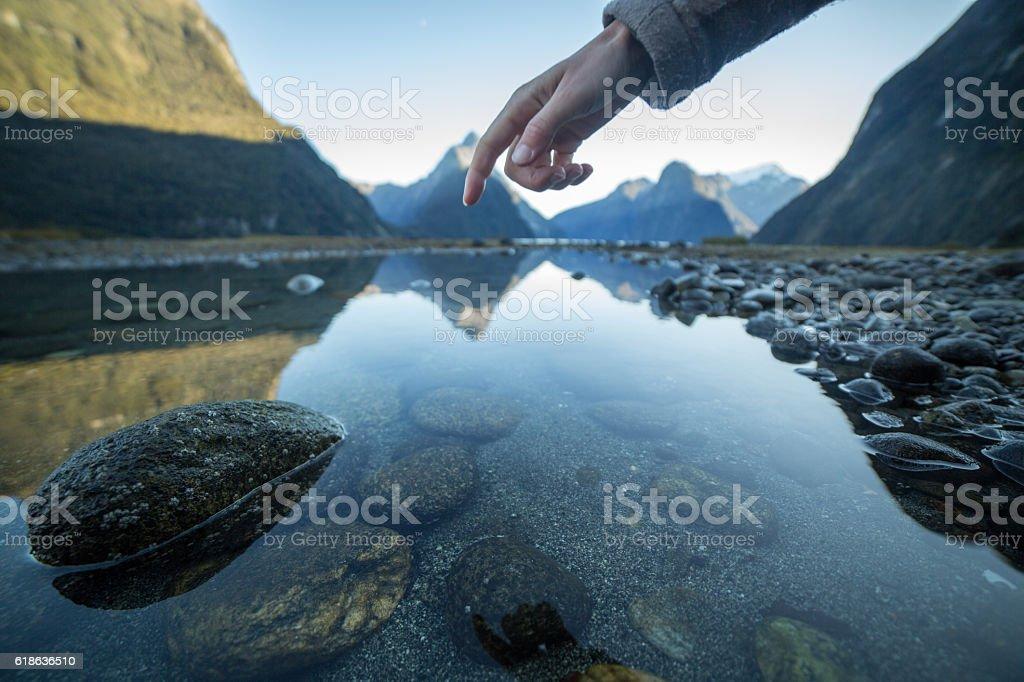 Finger touches surface of mountain lake stock photo