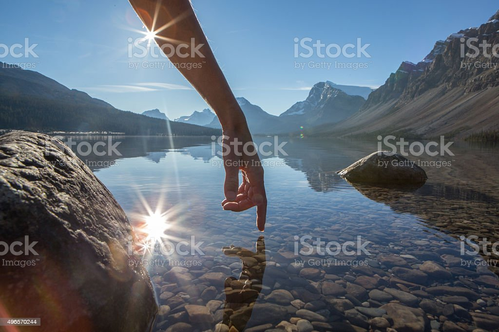 Finger touches surface of mountain lake, spectacular landscape stock photo