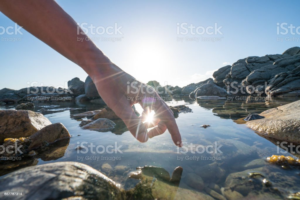 Finger touches surface of sea pond – Foto