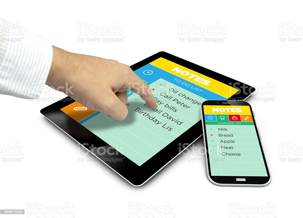 finger touching group of touchscreen devices with Note app stock photo