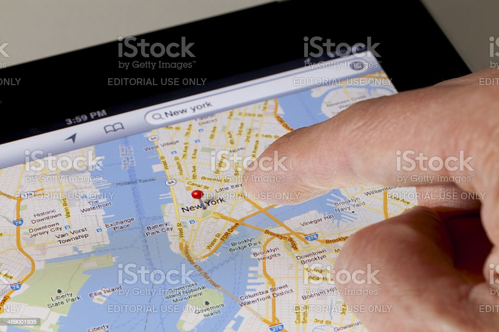 Finger using a map app on tablet stock photo