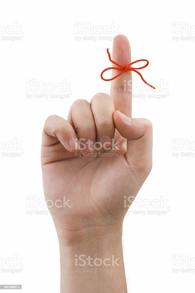 A finger with a red bow tied around it stock photo