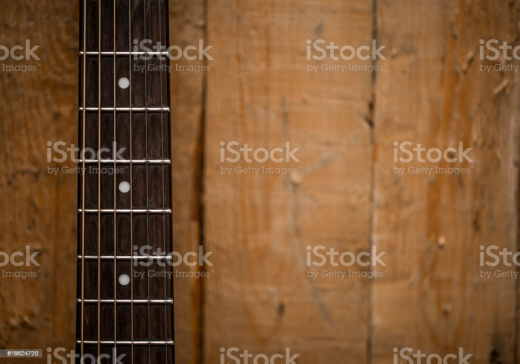 fingerboard from the acoustic guitar on wooden background stock photo