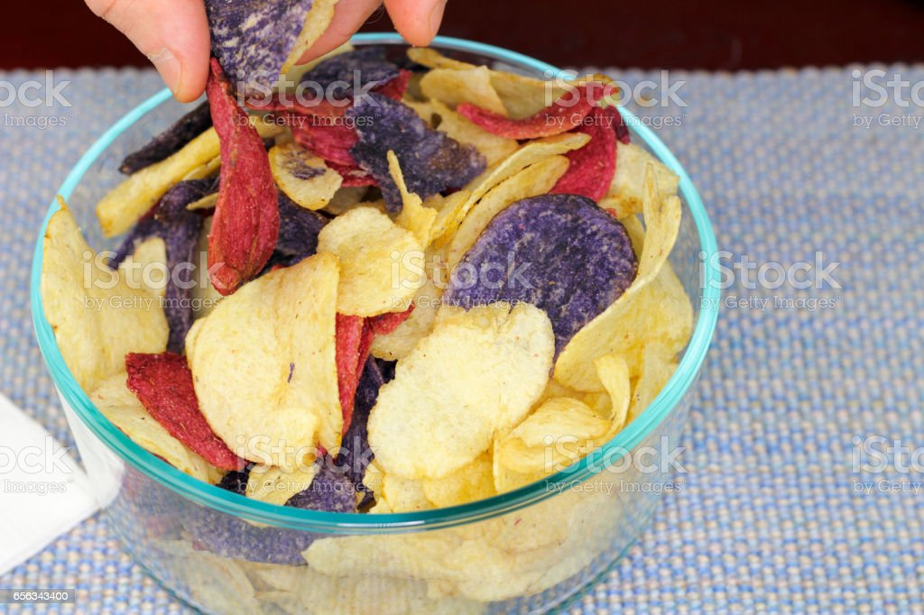Fingers Choosing Red, Purple and Yellow Potato Chips stock photo