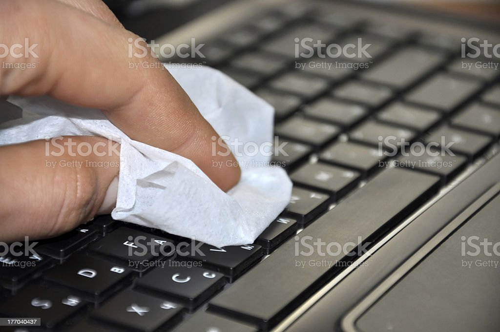 Fingers cleaning the keyboard of a digital notebook royalty-free stock photo