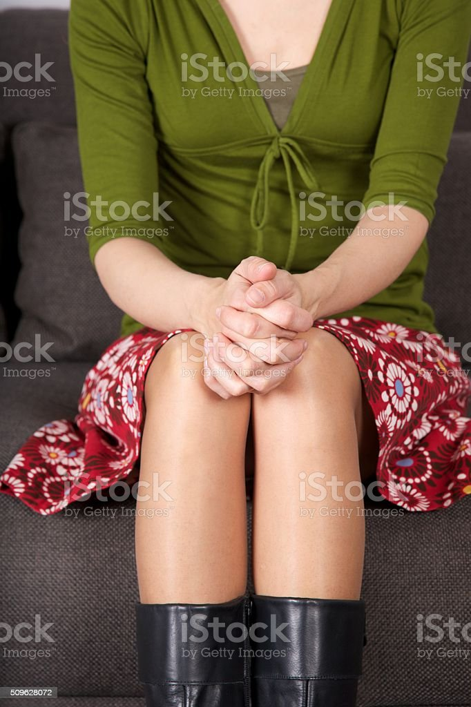 fingers crossed over knees stock photo