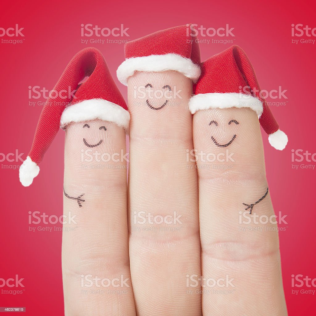 Fingers faces in Christmas Santa hats. Happy family celebrating concept royalty-free stock photo