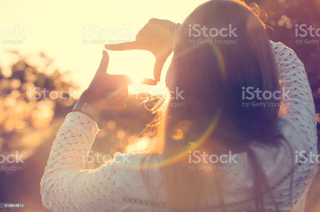 Fingers Framing the sun at sunset. stock photo