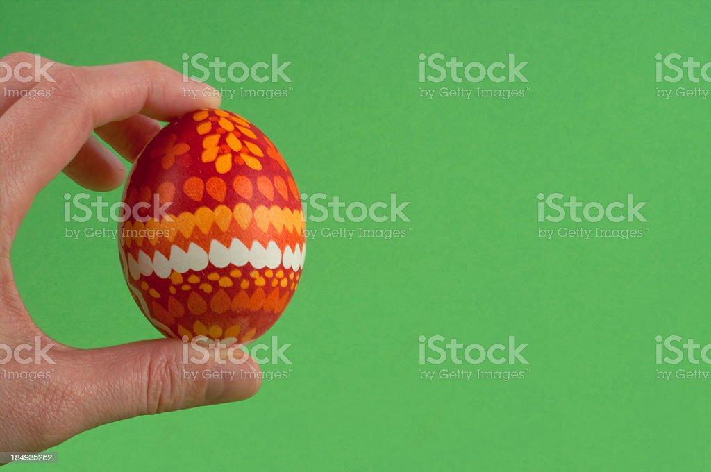 Fingers holding easter egg stock photo