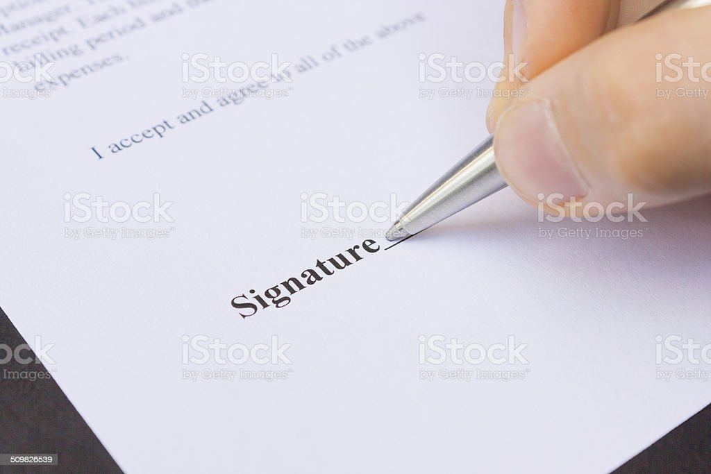 Fingers holding pen writing signature stock photo