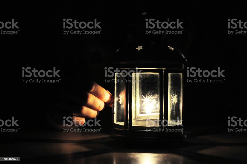 Fingers illuminated wirt light from candle lantern in dark, blac stock photo
