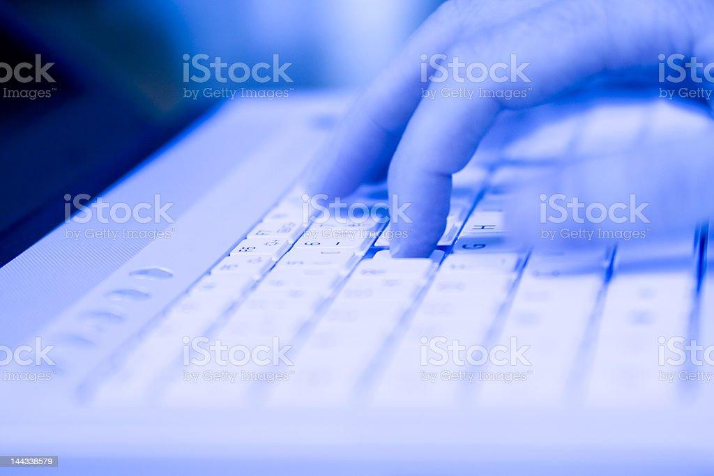 Fingers on keyboard in blue light stock photo