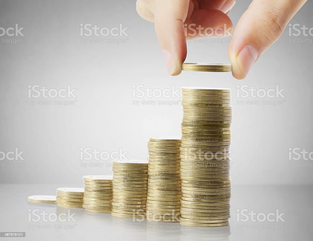 Fingers placing top coin on a stack of money stock photo