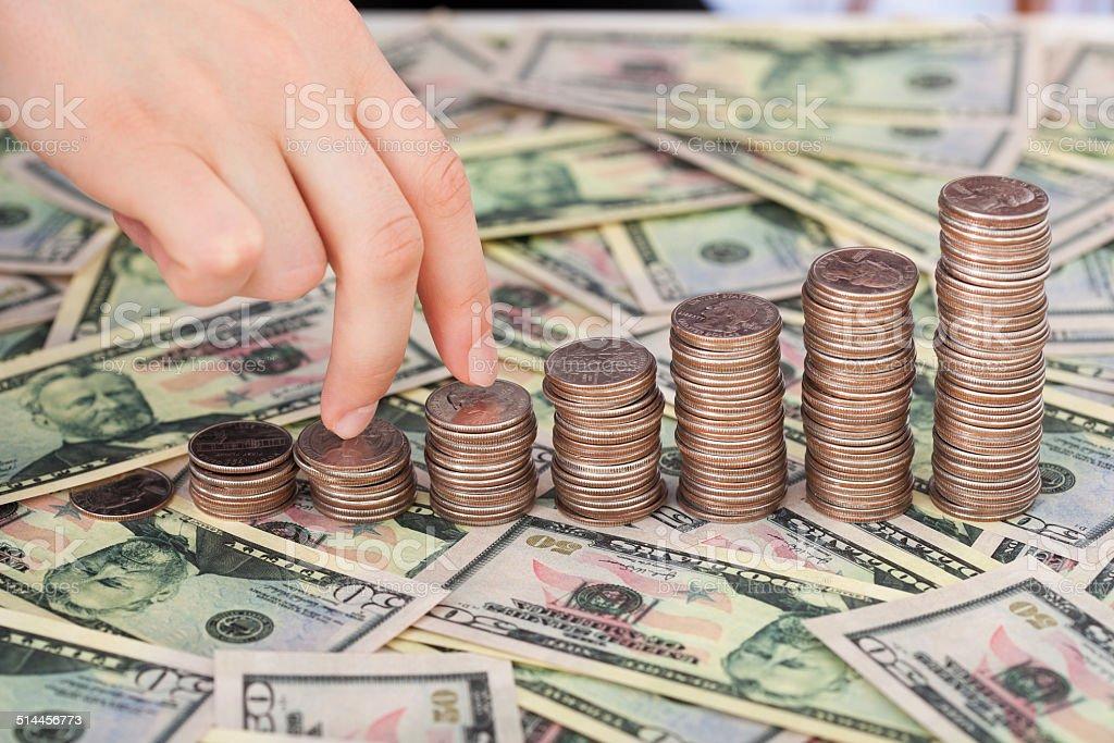 Fingers Walking Up Coinstack On Dollar Bills stock photo