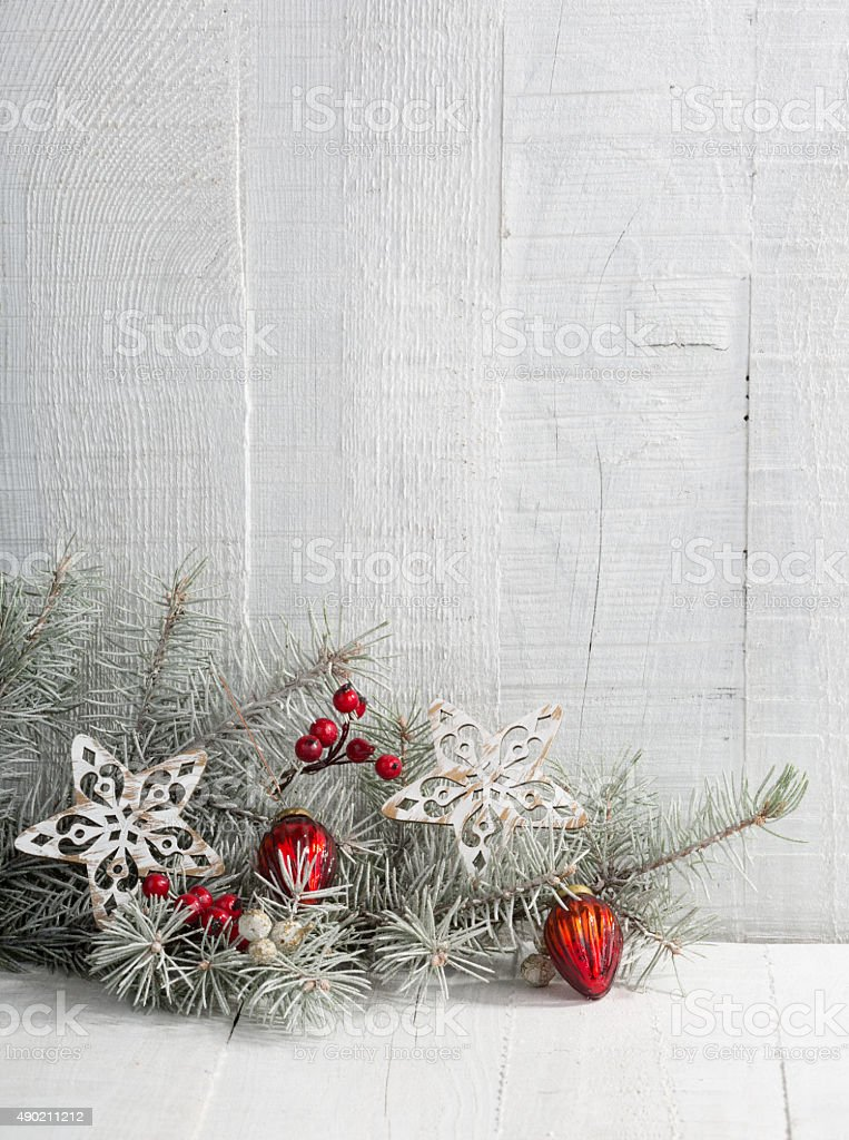 Fir branch with Christmas decorations on the wooden plank stock photo