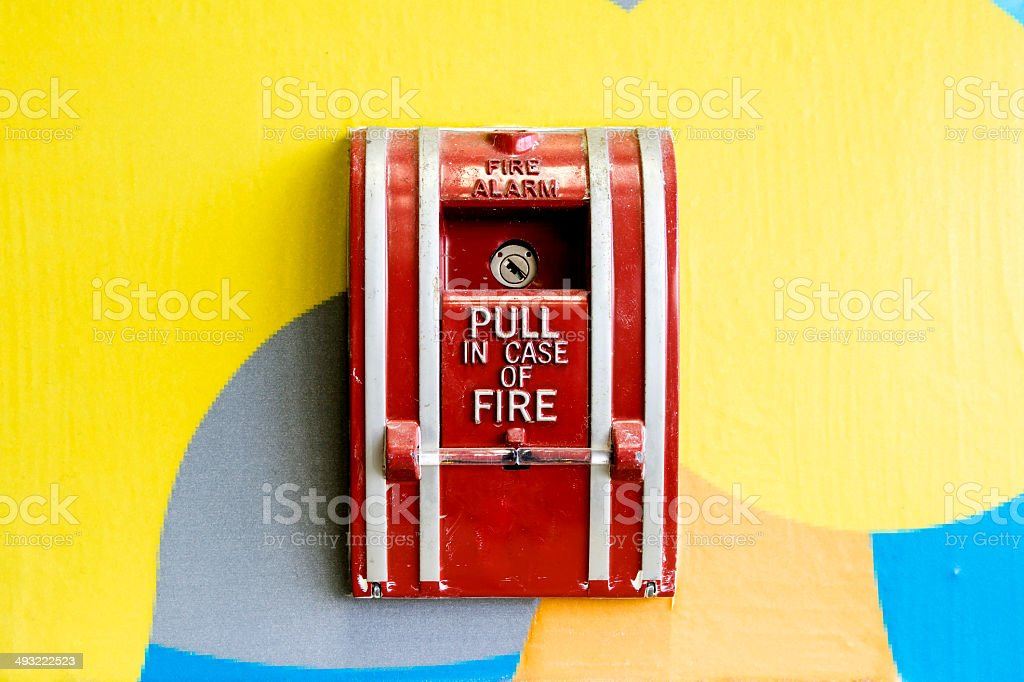 fire alarm box mounted on colorful wall stock photo