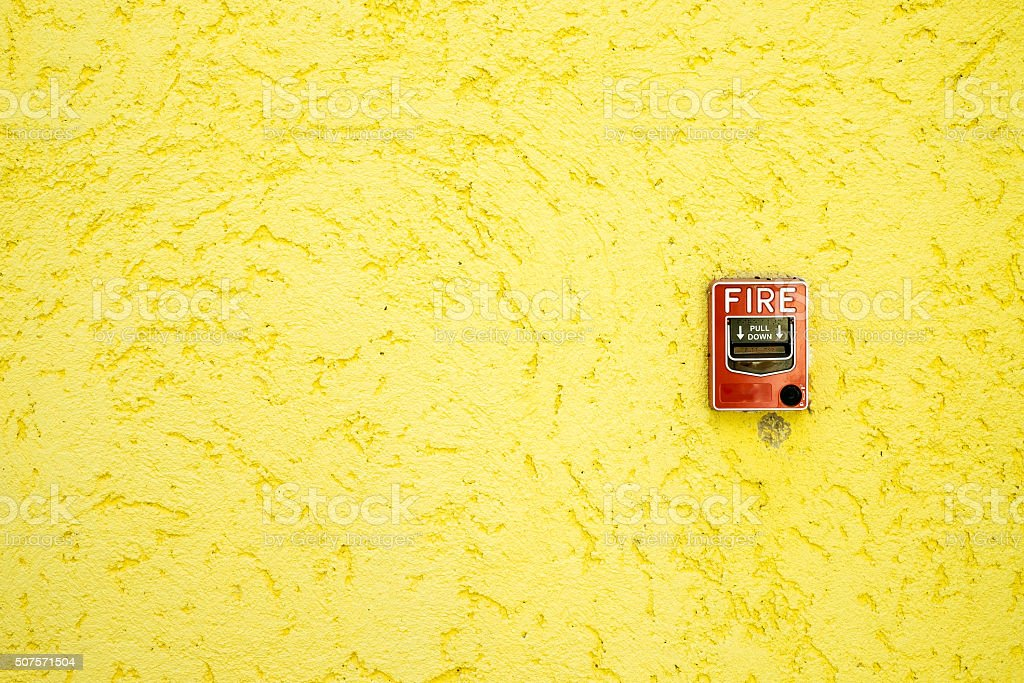 fire alarm box on yellow cement wall stock photo