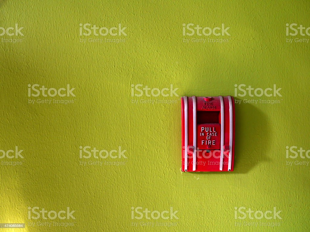 Fire alarm switch on green wall background. stock photo