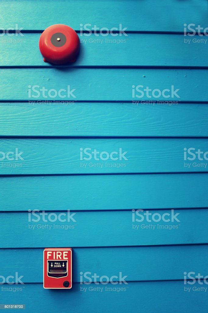 Fire alarm with blue painted wood background stock photo