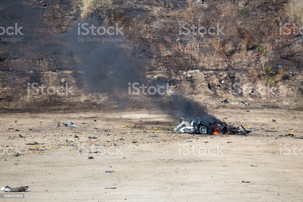 fire and car part blown away from car bomb investigation stock photo