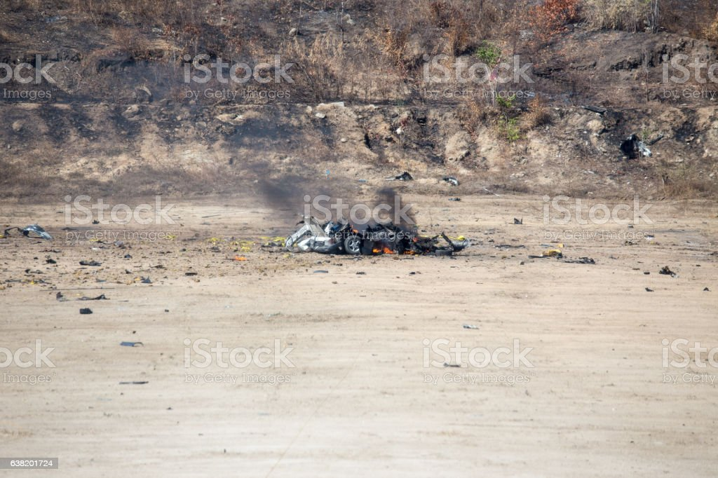 fire and car part blown away from car bomb training stock photo