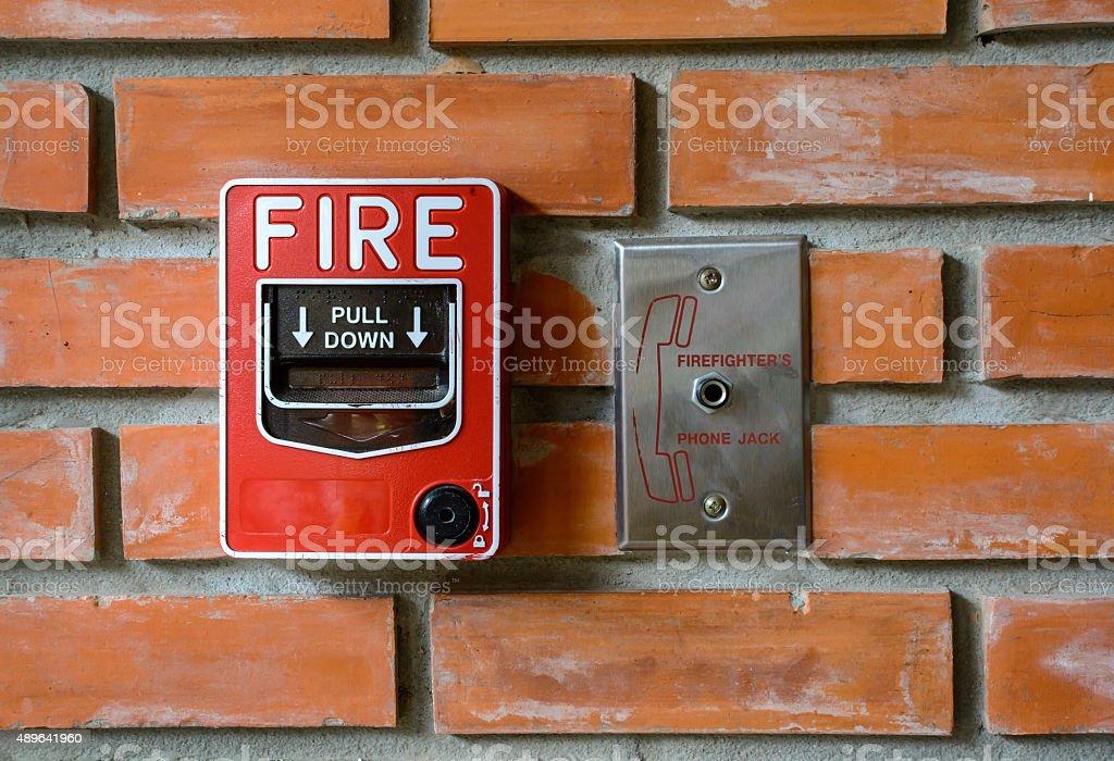 fire break glass alarm switch on brick wall stock photo