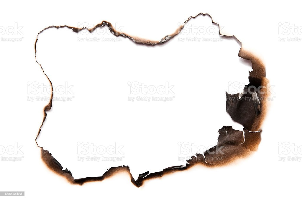 Fire burned hole in white paper stock photo
