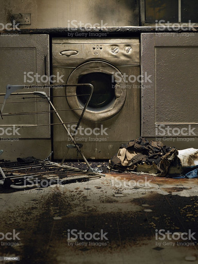 Fire damaged kitchen with washing machine and upturned clothes horse stock photo