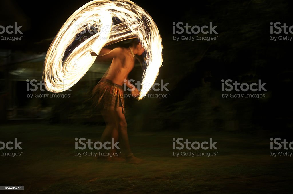 Fire Dancer Spins Torches on a Dark Beach stock photo