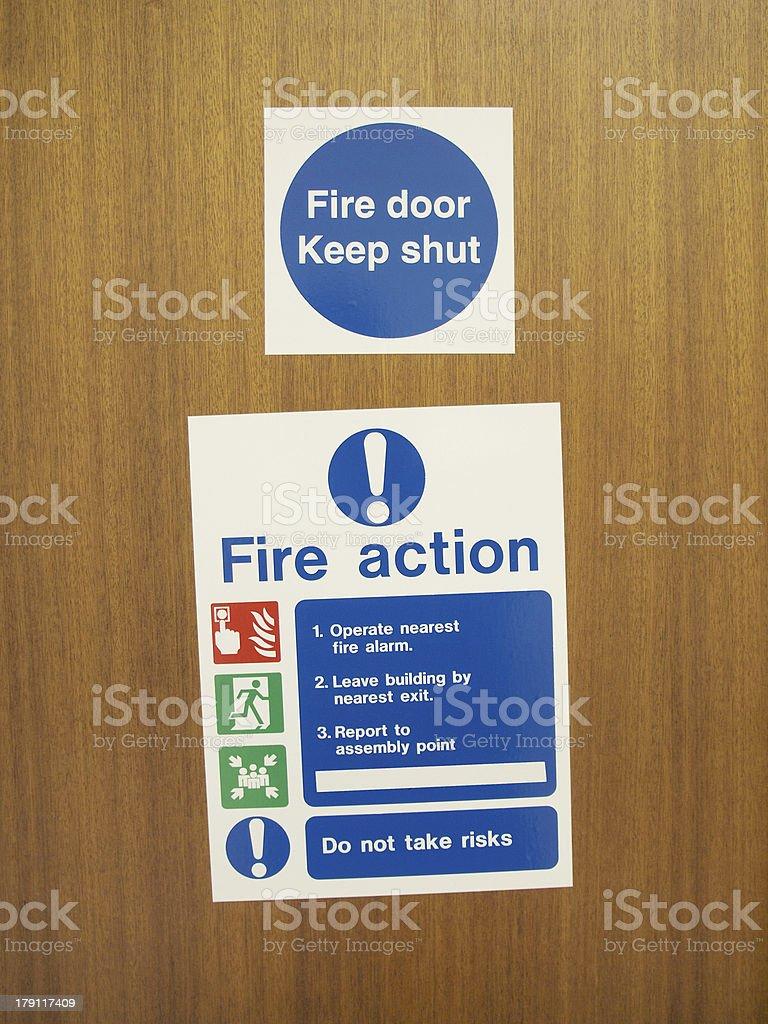 Fire door advice signs mounted upon a fire door  stock photo