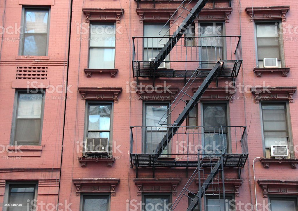 Fire Escape Steel Ladder on Urban Red House Facade stock photo