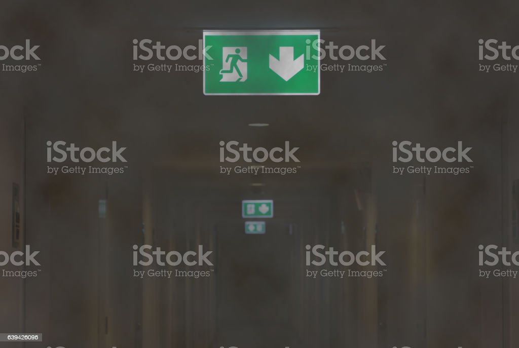 Fire Exit Light in Smoky Corridor of Apartment stock photo
