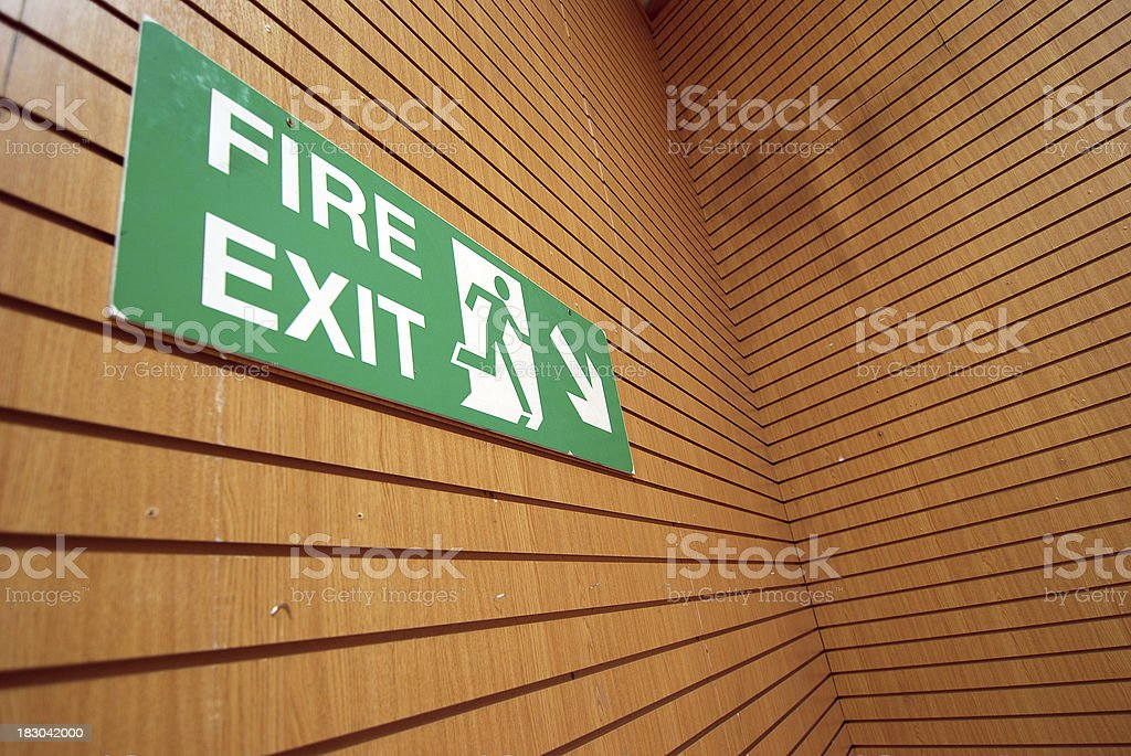 Fire exit sign on geometric wood wall stock photo