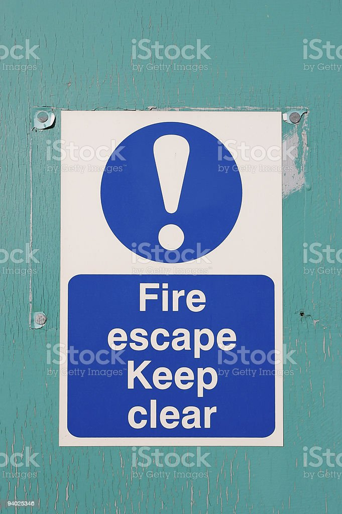 Fire Exit sign on green painted wooden door royalty-free stock photo