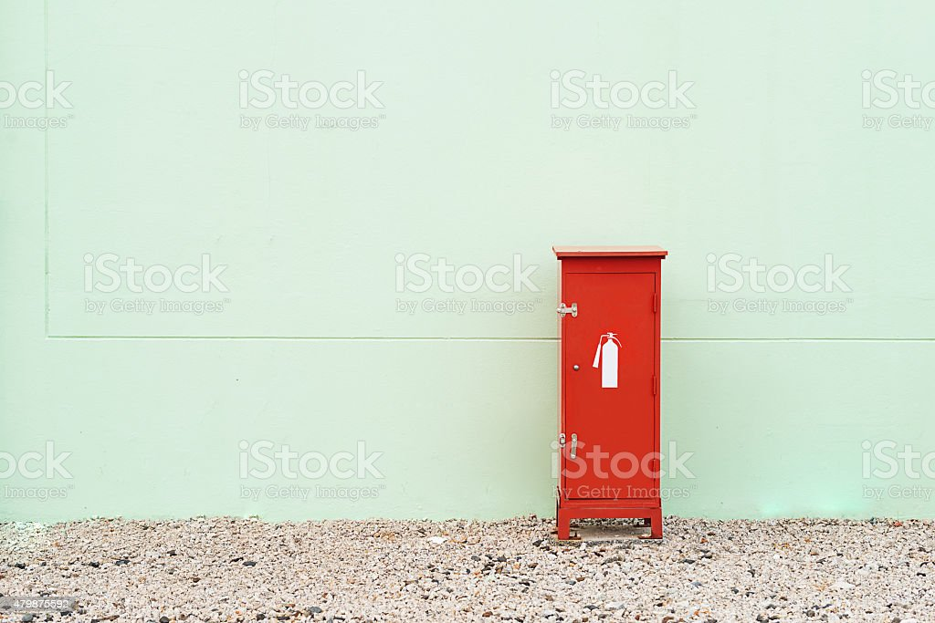 Fire extinguisher box at green wall stock photo