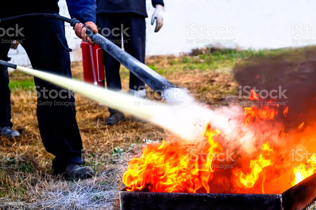 Fire Extinguishing with powder type fire extinguisher stock photo