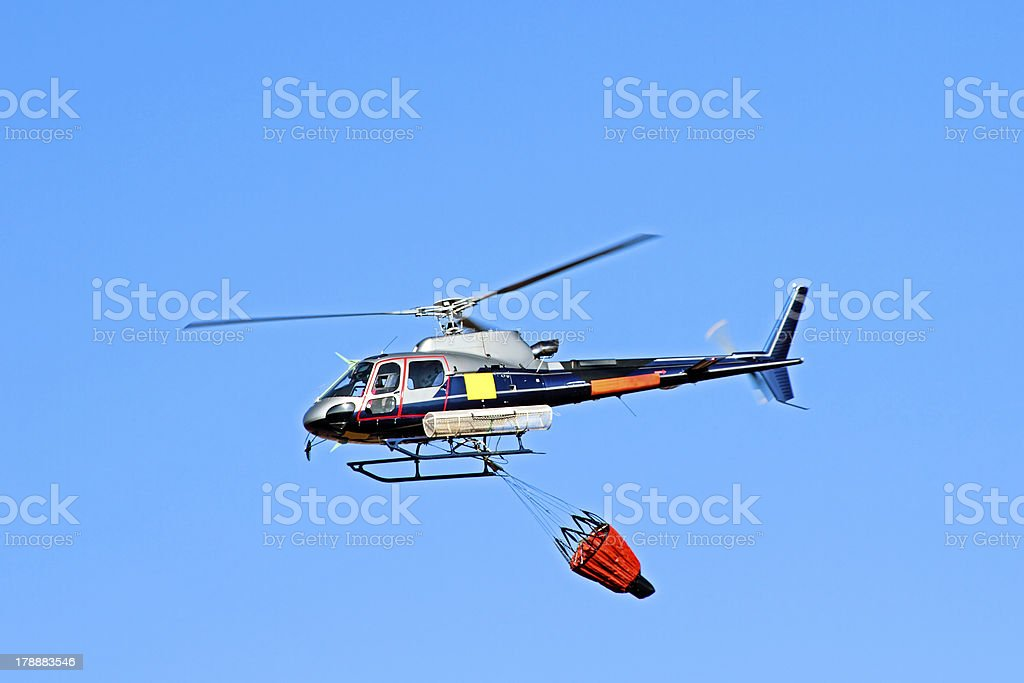 Fire fighter helicopter with a waterbag royalty-free stock photo