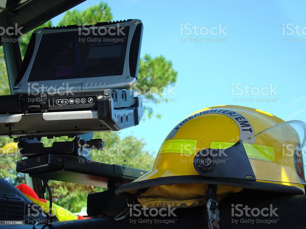 PC & Fire Fighter Helmet On Dashboard Of Engine stock photo