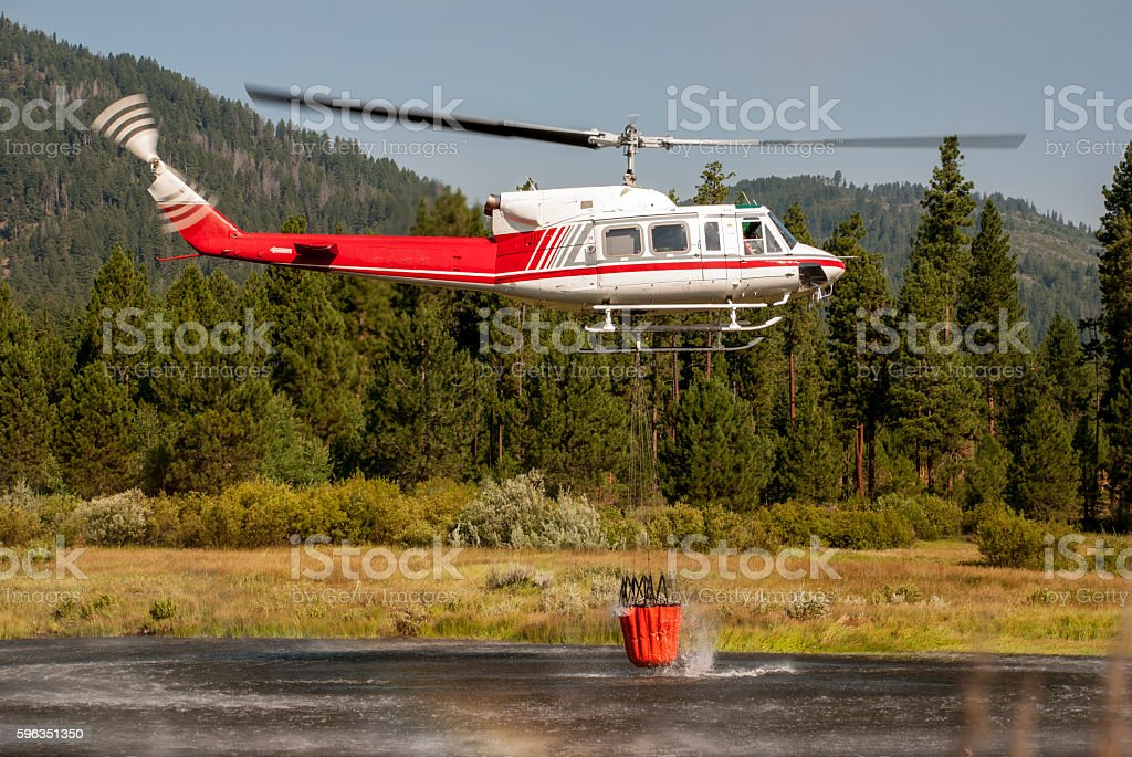 Fire fighter in a helicopter getting water from a lake stock photo